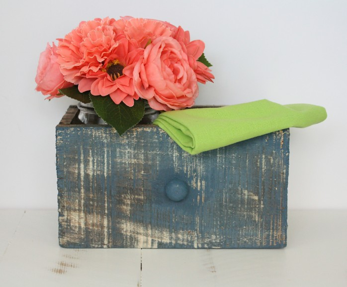 A weathered drawer with bright coral flowers